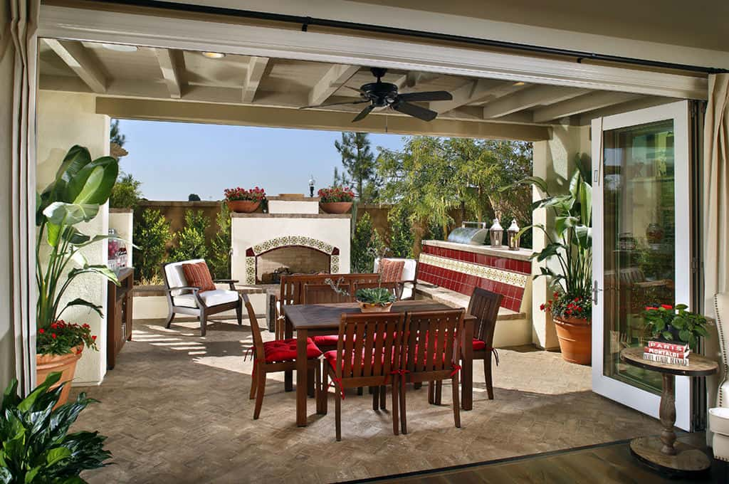 The doors to this open patio work by way of accordion-fold glass doors where homeowners can celebrate the comfortable climate of Irvine, Calif.<br /> <br /> Other features that make this outdoor space standout are its giant fireplace piece, unique red-tiled bench and cherry-stained dining table and chairs. The party possibilities are limitless.<br /> <br /> PHOTO COURTESY OF<br /> TRI Pointe Homes