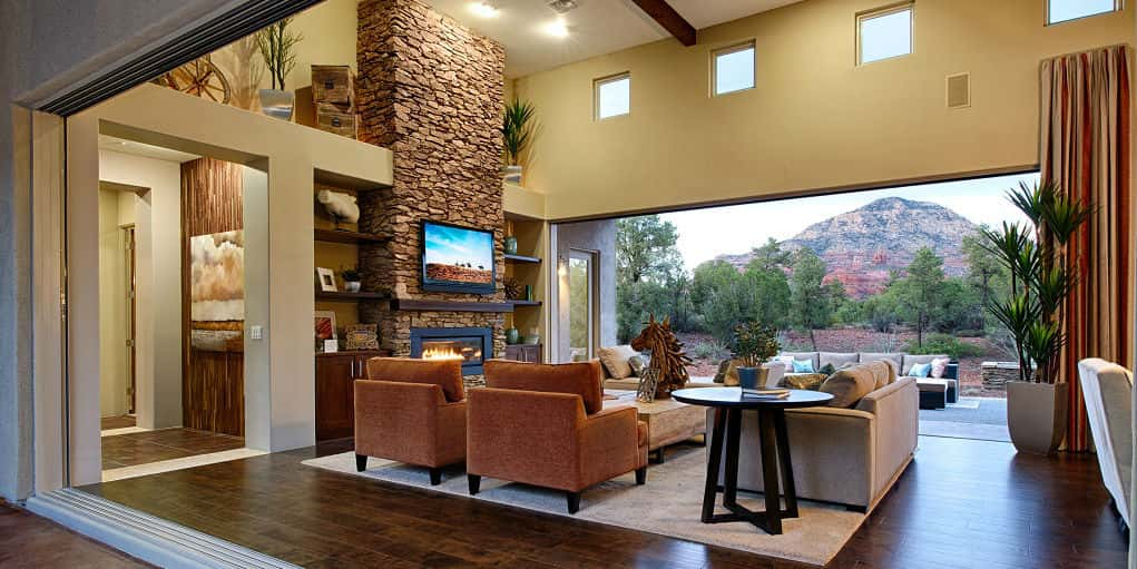 Where to begin in this breathtaking great room from Dorn Homes? Let's start with that view! A wall of glass puts this home at one with nature, which can be opened to create a space that blurs the line between indoors and out.<br /> <br /> We could also go on and on about the ceiling-high stone fireplace, adobe-style architecture, wonderful western accent accessories and more, but we'll leave that for you to ponder for yourself.<br /> <br /> PHOTO COURTESY OF<br /> Dorn Homes