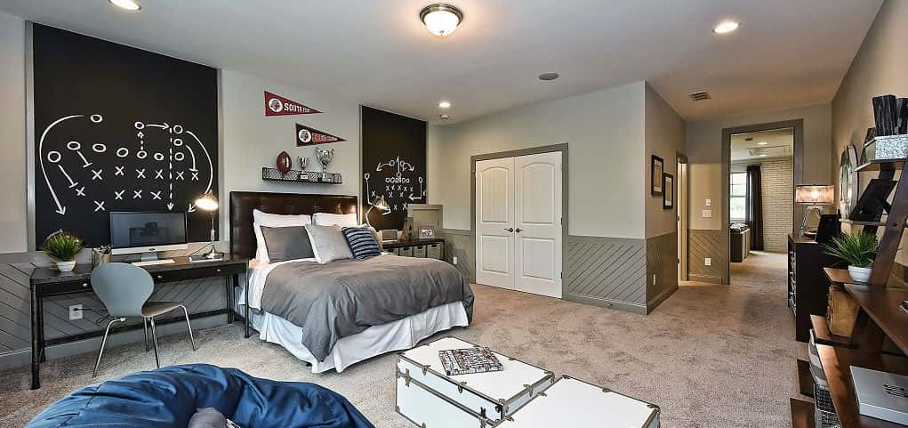 "Just outside of Charlotte, N.C., home of the Carolina Panthers, the Morgan's Branch community by <a href=""http://www.newhomesource.com/builder/av-homes/about/8011"" target=""_blank"" title=""Learn More About AV Homes"">AV Homes</a> really shows off its Panther pride with this football-themed bedroom.<br /> <br /> With plenty of shelving to show off trophies and two blackboard walls, perfect for planning out the next game-winning play, your football fan would love to touch down in a space like this.<br /> <br /> PHOTO COURTESY OF<br /> AV Homes"