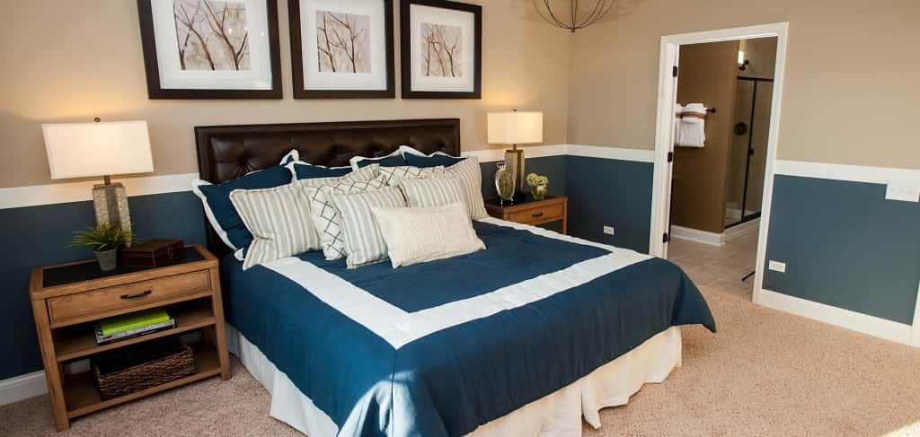 "<p>A two-toned wall and recessed ceilings make for a roomy owner's suite. ""It's very spacious and private,"" McCracken says. ""The laundry room is located just across the hall so there's less distance to carry a laundry basket.""<br /> <br /> The home's master suite includes a large master bath with an optional walk-in shower that can include a bench.</p> <p >PHOTO COURTESY OF<br /> Del Webb</p>"