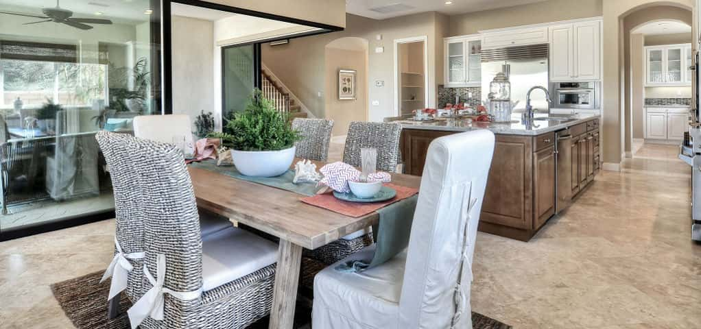 An open floor plan adjoins the breakfast nook and kitchen. A sizable fridge, stove top and double oven characterize this space, while a large island draws a crowd. Coral and gray accessories pull out the natural tones of the marbled flooring and cabinetry, while tie-back chairs add a softened, homespun look. <br /> <br /> A peek into the butler's pantry reveals one of this home's most popular upgrades, upper cabinets with patterned glass. Just up the stairs lies a game room with access to a sizeable balcony for entertaining.<br /> <br /> PHOTO COURTESY OF<br /> Melia Homes