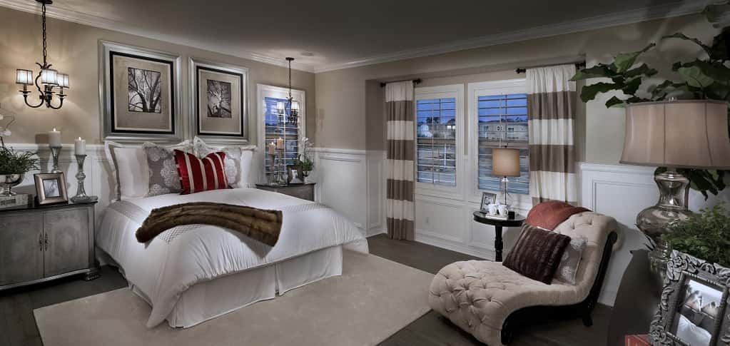 "White wainscoting and grey walls create a soft feel in the home's spacious master bedroom. ""It's so beautiful,"" DeVilbriss says. ""This floor plan offers a whole wing just dedicated to the master suite.""<br /> <br /> The space is large enough for a king-sized bed, a sitting room and large walk-in closets, a major plus for today's homeowner looking for ways to stay organized and tidy. Plenty of large windows bring in natural light for a comfortable resting area. ""The master bedroom is really isolated from the rest of the home, so it's something you can really retreat to.""<br /> <br /> PHOTO COURTESY OF<br /> Brookfield Residential SoCal<br />"