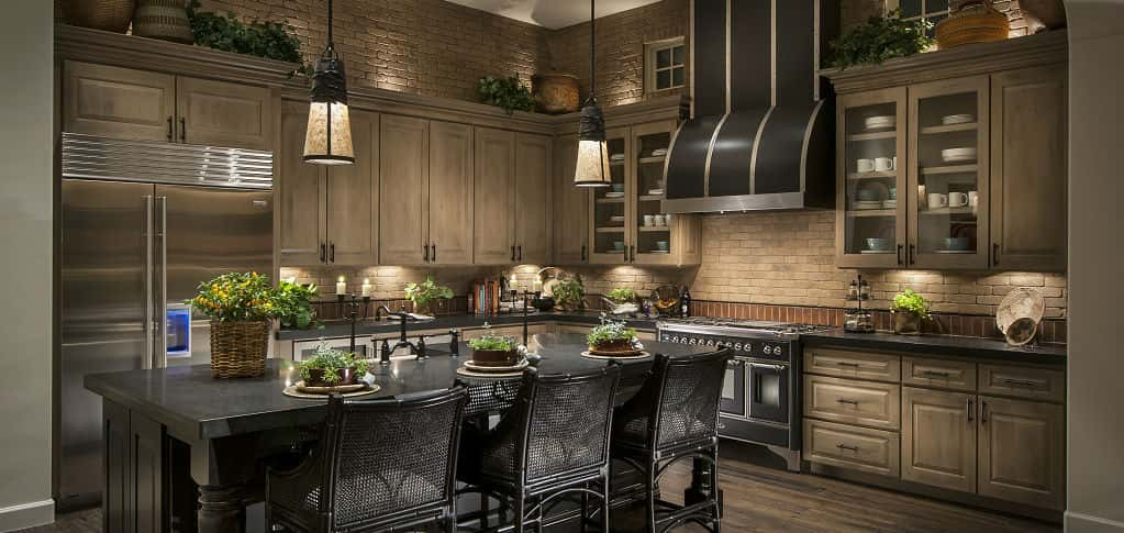 Brick walls, light brown cabinets and grey distressed wood floors bring a rustic look to an otherwise sophisticated kitchen. The kitchen, which includes a sizable island for dining or preparing food, is outfitted with luxurious flourishes. The stove and range hood, for example, were made just down the street from a Ferrari factory, Beckert says.<br /> <br /> PHOTO COURTESY OF<br /> Camelot Homes