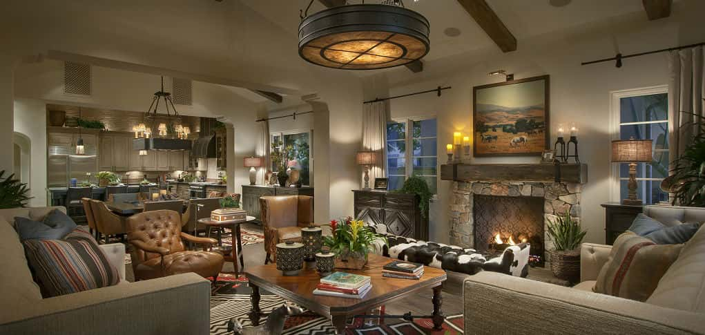 "A vaulted ceiling animates the home's great room, accented by a bold chandelier and a stone and wood beam fireplace. The expansive room is ideal for parties or other social gatherings, Beckert says.<br /> <br /> ""The great room is designed for how people live today,"" she says. ""Ninety-nine percent of our buyers want an open floor plan, so this is ideal for them. It has a nice flow from the great room to the dining space down to the kitchen.<br /> <br /> PHOTO COURTESY OF<br /> Camelot Homes"
