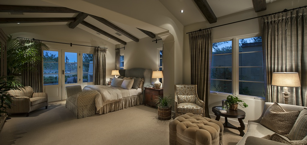 The vaulted ceilings are carried over into the home's master bedroom, which includes a spacious sitting area for a room-within-a-room feel. Dark wood beams contrast with the room's light grey walls for a soothing note.<br /> <br /> Two French doors make it easy to access the home's outdoor spaces while six large windows deliver plenty of natural light.<br /> <br /> PHOTO COURTESY OF<br /> Camelot Homes<br />