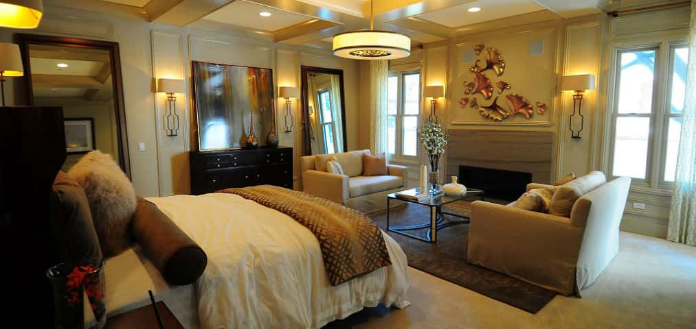 This stunning master bedroom provides residents with the perfect sanctuary to relax and unwind after a long day. The generous space includes plenty of room for a sitting area for enjoying a book or glass of wine and continues into a private balcony. Architectural details such as the picture frame molding on the walls and a coffered ceiling add a touch of elegance to the overall design.<br /> PHOTO COURTESY OF<br /> Insignia by City Ventures