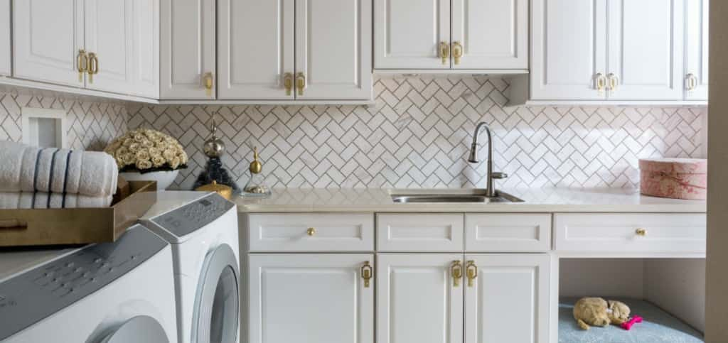 The laundry room may be the last place you think of decorating, but adding an attractive light fixture and elegant touches can improve your experience in the room. Designer Paula Grace of Ashburn, Va., added luxurious wallpaper, a tile backsplash and elaborate hardware on the cabinets to update the Design House laundry room.<br /> <br /> Grace painted the ceiling sky blue since the room doesn't have natural light, created a functional open closet with bins for family members' laundry and then introduced a few pretty accessories and a speaker so you can listen to music while you work.<br /> <br /> <strong>PHOTO BY</strong><br /> Angie Seckinger