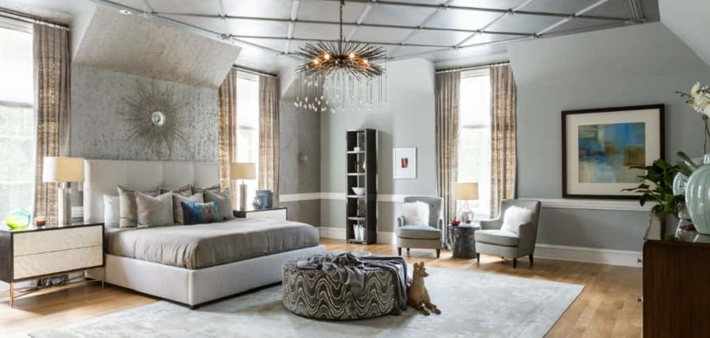 <p><span>While large master bedroom suites are a luxury, they can also challenge your ability to make them both glamourous and warm. Designer Dennese Guadeloupe Rojas of Silver Spring, Md., transformed a huge bedroom with a high ceiling into a cozier space by painting the ceiling a slightly darker gray than the walls.</span></p> <p><span> </span></p> <span>Rojas added a touch of beading and metals along with a slightly sparkly overcoat to the walls and ceiling for a modern, yet elegant, style and layered plush fabrics on the floor, around the windows, on the chairs and on the bed for warmth.<br /> <br /> <strong>PHOTO BY</strong><br /> Angie Seckinger</span>