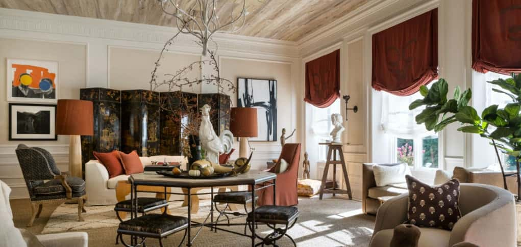 <p><span>Designer Josh Hildreth of Reston, Va., mixes a statement mirror with antler horns, tall textured wood floor lamps, a chandelier of sculptural branches with lush embroidered curtains and comfortable couches and chairs upholstered in hide and leather to provide ballast for this large family room.</span></p> <p><span> </span></p> <span>Overhead, the ceiling features removable wallpaper cut into strips to resemble wood planks. Sculptures provide an artistic balance to the rustic objects and layered carpet underfoot adds to the sense of richness in the space, which is accented with rust-toned fabrics and shades.<br /> <br /> <strong>PHOTO BY</strong><br /> Angie Seckinger</span>