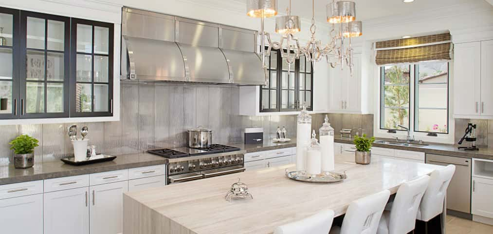 "An expansive limestone island, stainless steel commercial-style range hood and exquisite clear glass backsplash are just a few of the focal points in this kitchen. Sleek and sophisticated, this kitchen displays the best in form and functionality. White and clear-glass cabinets give the room an airy feel without feeling sterile. Any home cook would love to entertain in this kitchen, which inspires creativity and a bit of indulgence (a little more dessert, you say?).<br /> <br /> PHOTO COURTESY OF<br /> Davidson Communities<br /> <br /> <a href=""https://www.newhomesource.com/communityresults/market-30/brandid-4554"" target=""_blank"">Davidson Communities in Rancho Mirage, Calif.</a>"