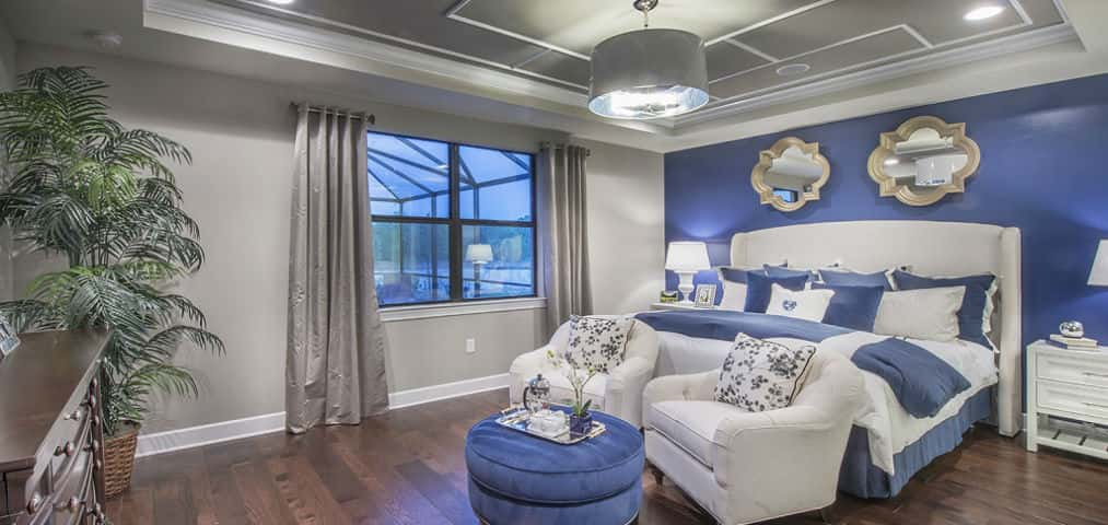 "A blue accent wall and grey and white geometric tray ceiling add pop to the home's owner's bedroom. Large windows face out to the home's covered lanai.<br /> <br /> When it comes to tray ceilings, owners can get creative. ""Buyers love how they have the opportunity to display their own taste or personality by decorating the inside of the tray ceiling (as shown here),"" says Hawley.<br /> <br /> PHOTO COURTESY OF<br /> DiVosta Homes"