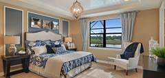 A beautiful, very elegant and classy master bedroom overlooking a lake with cream, white and blue decoration over a cream rug. There's a matching bed and dark wood furniture.