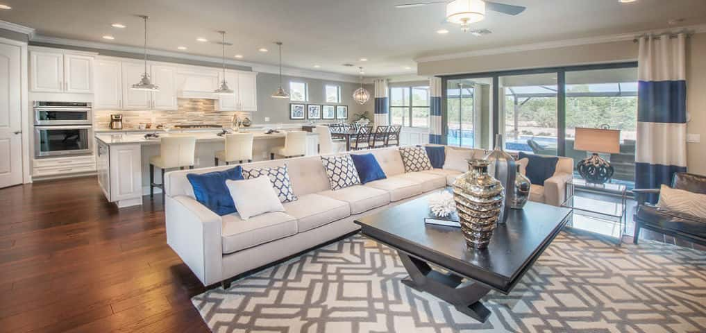 "A crisp white and blue color scheme throughout the gathering room, kitchen and café exaggerates the space in the open floor plan arrangement. Large windows and glass sliding doors provide ample amounts of natural lighting in this primary area.<br /> <br /> ""The (Pinnacle) plan maximizes space in the areas where homeowners spend most of their time — the kitchen and gathering spaces,"" Hawley says.<br /> <br /> PHOTO COURTESY OF<br /> DiVosta Homes"