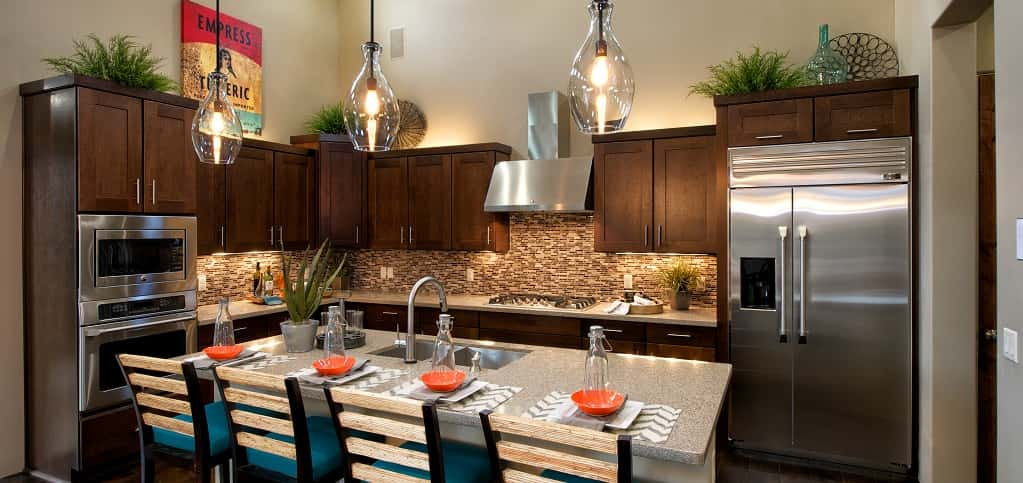 "Taking cues from surrounding landscape in Sedona, Ariz., this kitchen utilizes neutral colors for a relaxed and inviting feel. Placed high, three over-island glass pendant lamps subtly bring charm into the home's bright kitchen. A multicolored tile backsplash and high ceilings give this kitchen a warm and inviting feel. The kitchen's island is the perfect place to enjoy watching the home cook or even offering a little help, especially during holidays.<br /> <br /> PHOTO COURTESY OF<br /> Dorn Homes<br /> <br /> <a href=""https://www.newhomesource.com/communityresults/market-17/brandid-4171"" target=""_blank"">Dorn Homes in Sedona, Ariz.</a>"