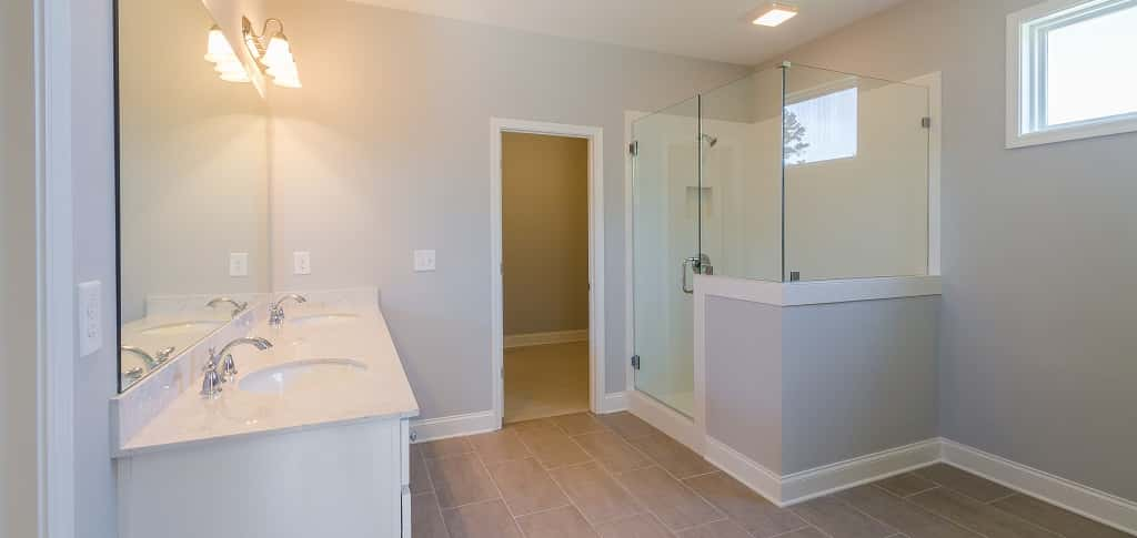 A glass-encased shower, double vanities and long, rectangular floor tiles give this master bathroom an elegant look.<br /> <br /> A horizontal window high on the wall provides sunlight and privacy.<br /> <br /> PHOTO COURTESY OF<br /> Edward Andrews Homes