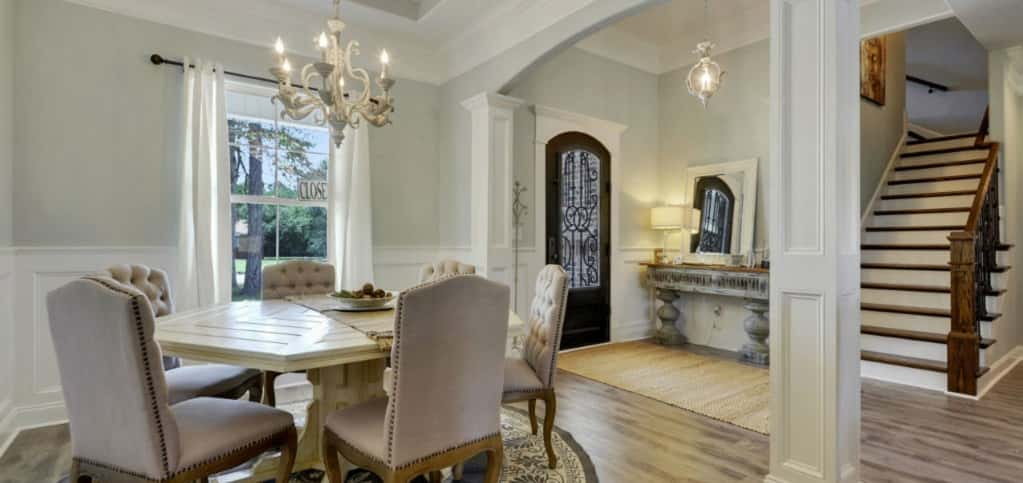 "<p>A coffered ceiling, wainscoting and recessed panel columns evoke the sense of a dinner party from the 1920s in this elegant formal dining room. That's the point, says Siemiontkowski. ""It is important to distinguish our homes from the rest by adding elegant details not seen in"" other homes. ""You will also see elegant door casings in our homes that feel like they were handcrafted many years ago.""<br /> <br /> Features such as the coffered ceiling and chandelier come standard in this home.</p> <p >PHOTO COURTESY OF<br /> Elliott Homes</p>"