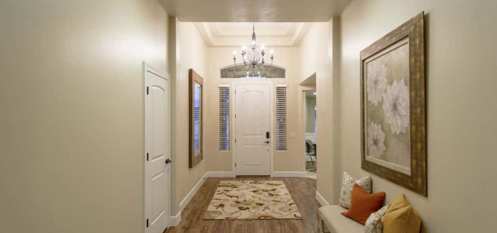 High ceilings, a window above the door and two long vertical windows along each side of the front door provide plenty of natural light for the home's entryway. A classic chandelier and small hallway allow guests to get a feel for what's to come in the rest of this home.<br /> <br /> PHOTO COURTESY OF<br /> Ence Homes