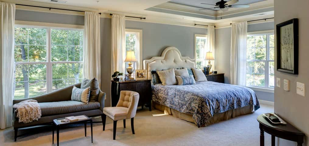 "Wide windows, white treatments and a great view are what make this master bedroom in the <a href=""https://www.newhomesource.com/resourcecenter/slideshows/home-of-the-week-oxford-plan-by-evergreene-homes"" target=""_blank"" title=""Oxford Plan"">Oxford Plan </a>by <a href=""https://www.newhomesource.com/builder/evergreene-homes/about/6704"" title=""Evergreene Homes"">Evergreene Homes</a> stand out from the crowd. If light is what makes you feel alright, take a peek at this master suite.<br /> <br /> Blue walls and a vaulted ceiling paired with a bold comforter makes this room pop when light is let in. Contrasting dark furniture adds the perfect final touch so all is not washed out from the abundance of natural light.<br /> <br /> PHOTO COURTESY OF<br /> Evergreene Homes"