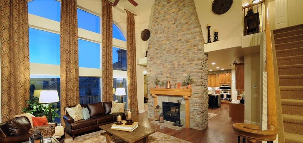 "The focal point of the Dynasty is the oversized great room. ""The Dynasty was designed to enhance main level living in a two-story floor plan,"" says Kim Sandoval, marketing director for Classic Homes.<br /> <br /> From the warm hardwood floors to the stunning two-story stone fireplace and window wall, the great room will have guests imagining they have just stepped into a beautiful mountain lodge.<br /> <br /> PHOTO COURTESY OF<br /> Classic Homes<br />"