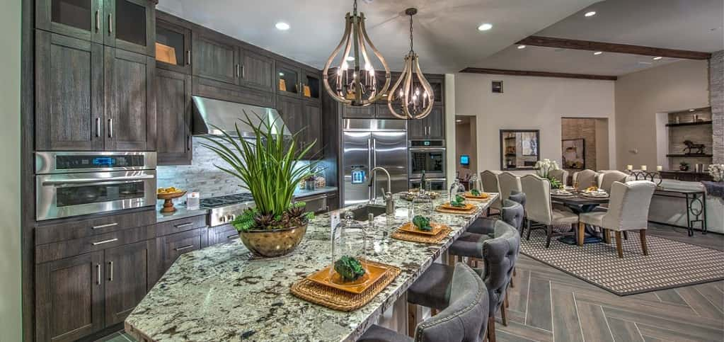 Wouldn't you love to entertain in this kitchen with metal teardrop pendant lights and rustic-style cabinets? A large island easily sits four while still allowing for enough work space to cook, bake or create libations.<br /> <br /> With chevron-like patterned tile and stainless steel appliances, the kitchen is both modern and inviting.