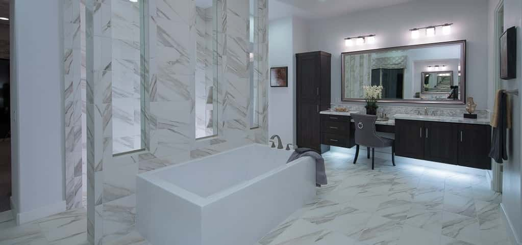 White tile with streaks of gray is used in the master bathroom to create an artistic and luxe space to wash away the day's troubles.<br /> <br /> A stand-alone soaking tub sits in front of an enclosed shower and one of two vanities in the bathroom. This floating vanity includes a sitting area to complete one's beauty routine.