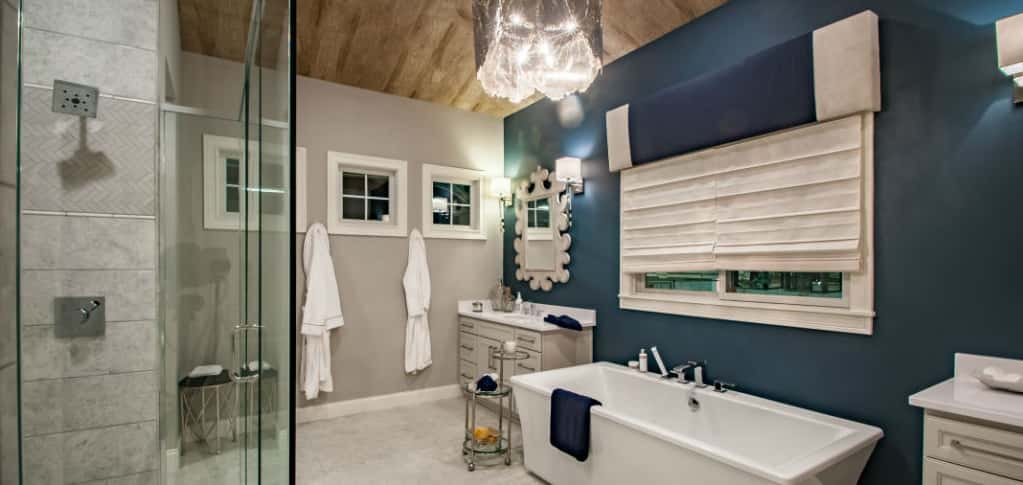 A blue accent wall contrasts perfectly white tile floors in the master bathroom of the Rookwood plan. It's easy to unwind in the soaking tub or the glass-encased shower.<br /> <br /> White double vanities ensure this luxe bathroom stays neat with plenty of storage and space for needed toiletries for everyone.<br /> <br /> PHOTO COURTESY OF<br /> Fischer Homes