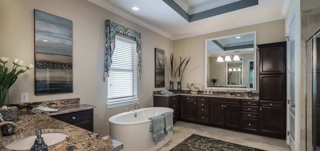 <p>A stand-alone tub next to a large window and a coffered ceiling are the highlight of the sizable master bathroom. The bathroom includes a separate shower and dual vanities for added convenience.<br /> <br /> This model has two separate walk-in closets so homeowners have plenty of space for clothing and accessories.</p> <p >PHOTO COURTESY OF<br /> GreenPointe Homes</p>
