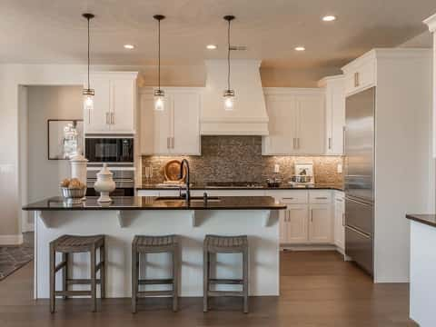 A brown and tan tile backsplash and white custom range hood are focal points in the kitchen of the Ebony Plan by Cole West Homes. Located at Brio in Washington, Utah.