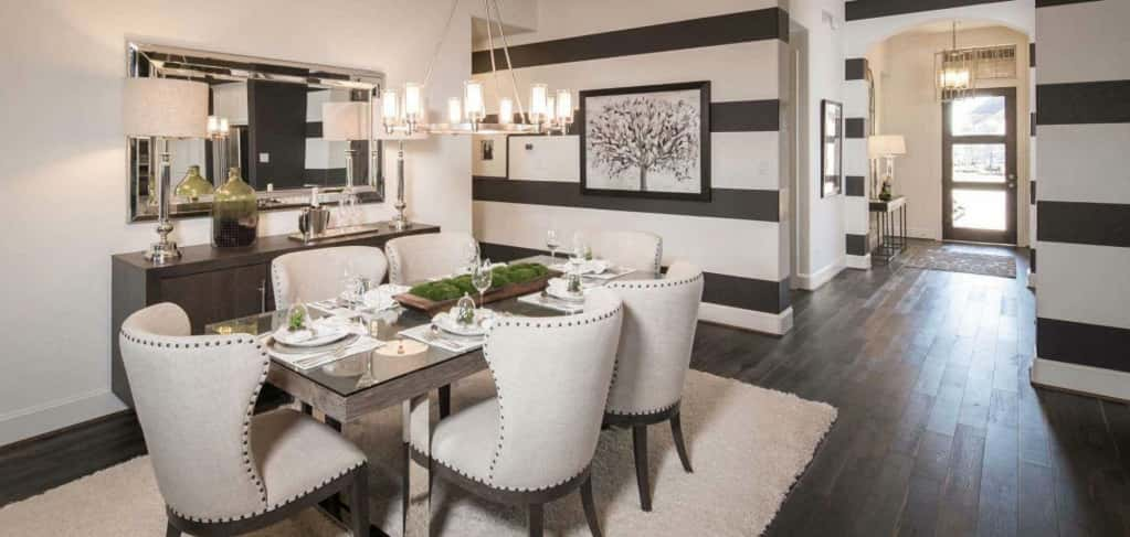 """The dining room is open to the family room and kitchen,"" says Tiffany Amore, marketing manager for Highland Homes. ""It's important to have this space to center the family together for meals, buyers like that it is open though so it can be a shared space. <br /> <br /> Loving the black and white striped walls, which accentuate the white dining chairs and gray dining table. A classy metal chandelier hangs above the table, while a large mirror above a buffet table makes this room feel more spacious. <br /> <br /> <strong>Photo Courtesy of</strong><br /> Highland Homes"