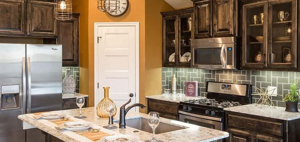 The Ivory plan's kitchen features so many great stylish and functional qualities. Glass-front cabinets allow homeowners to display cherished china and other items, while a pantry provides much-needed storage for appliances, canned and dry goods and more.<br /> <br /> Olive glass tiles are an attractive backsplash in this kitchen and a kitchen island seats three. Stainless steel appliances provide a sleek, clean look.<br /> <br /> <strong>PHOTO COURTESY OF</strong><br /> Ideal Homes