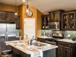 The Ivory plan's kitchen features glass-front cabinets, a pantry, an olive glass tile backsplash, stainless steel appliances and a kitchen island. By Ideal Homes at Trail Woods in Norman, OK.