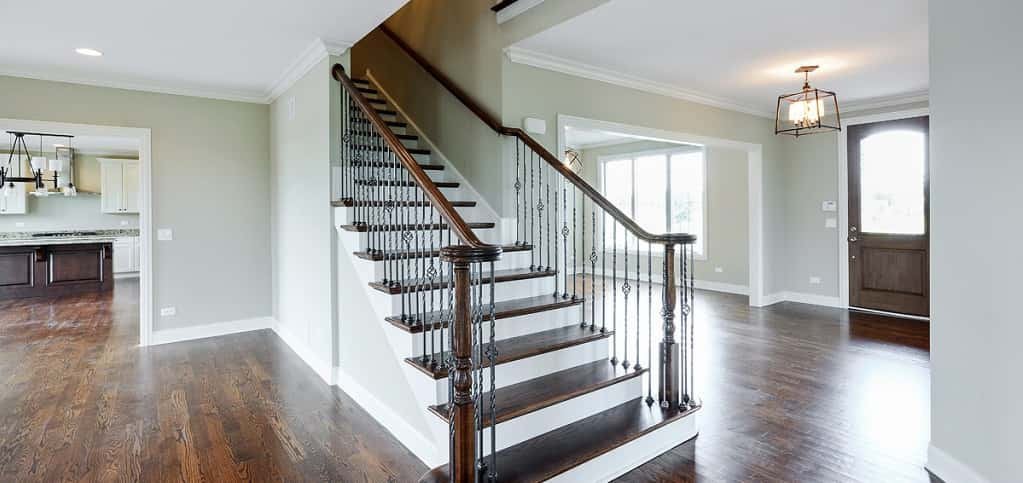 "<p>The home's spacious foyer is highlighted by a grand solid oak staircase with wrought-iron balusters, giving guests a stunning first impression of what's to come.<br /> <br /> ""The foyer welcomes guests into your home,"" says Kelly Daiberl, a design consultant for Kinzie Builders. ""Aside from the exterior, it is the first impression a visitor will receive. ""I also provides a main pint of circulation to the different rooms.""</p> <p> </p> <p>PHOTO BY<br /> VHT Studios</p>"
