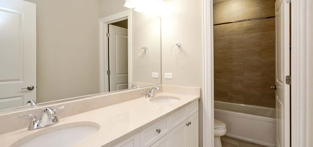 <p>The Oak's master bath includes dual marble countertops, large-format porcelain tile, Kohler faucets and fixtures, a spacious shower with a frameless enclosure and glass/stone accents, a soaking tub and champagne-toned chandelier with a fabric shade and glass accents.<br /> <br /> To create an even more luxurious feel, owners can upgrade to quartz countertops and larger tiles.</p> <p> </p> <p>PHOTO BY<br /> VHT Studios</p>