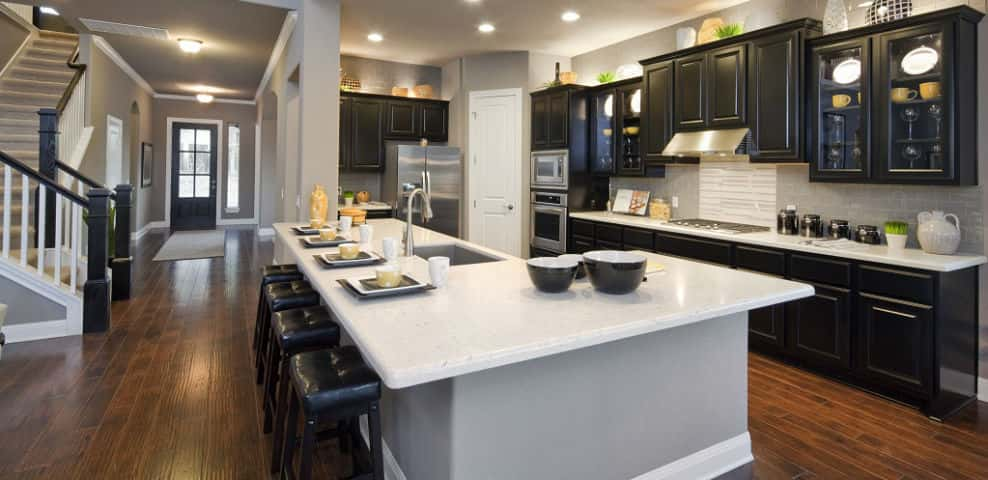 "<p>With a Silestone countertop, rather than granite, and a glass tile backsplash, this kitchen is a great example of modern design.<br /> <br /> Beyond looking good, Onken says, it's great for entertaining. ""There's this huge island where lots of people can fit. You have ample room for putting meals together, serving food and it's a place where guests can mingle.""<br /> <br /> PHOTO COURTESY OF<br /> Jimmy Jacobs Custom Homes</p> <p ><a href=""https://www.newhomesource.com/resourcecenter/articles/secrets-from-a-model-home-design-pro"" target=""_blank"">Check out a video tour of the kitchen.</a></p>"