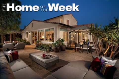 Outdoor living space with home in the background and Home of the Week overlayed on the photo