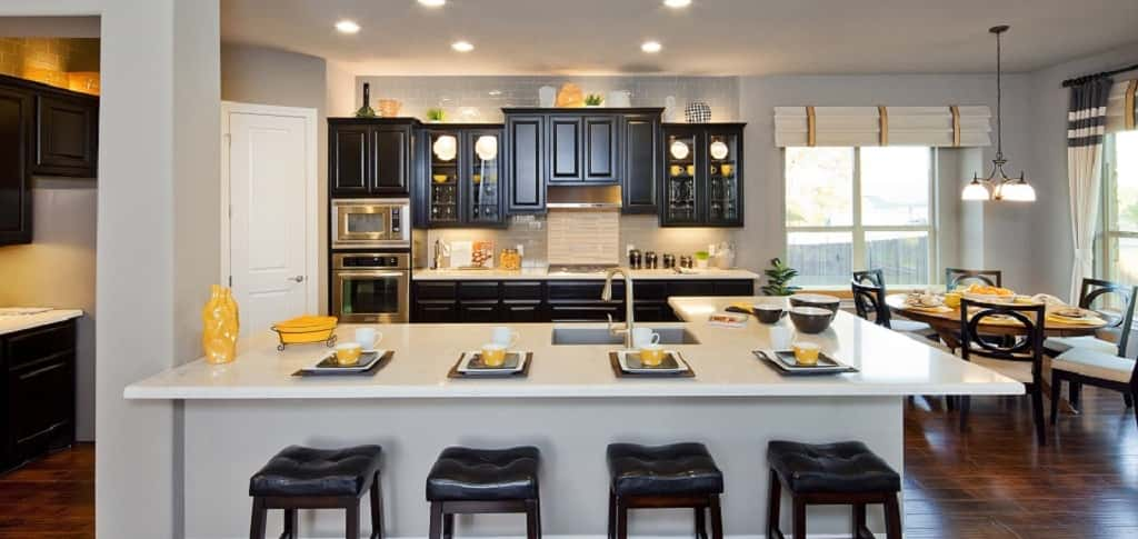 "Pops of yellow and dark brown bring this kitchen to life, making this area one that brings positive energy to homeowners. A Silestone L-shaped island and a clear glass subway tile backsplash are clean touches in this bright space by <a href=""https://www.newhomesource.com/builder/jacobs-homes/about/16562"" title=""Jimmy Jacobs Homes"">Jimmy Jacobs Homes</a>. A breakfast nook fills the need for dining space when the kitchen island is too informal — or overcrowded. This kitchen's layout is ideal for entertaining for any occasion.<br /> <br /> PHOTO COURTESY OF<br /> Jimmy Jacobs Custom Homes<br /> <br /> <a href=""https://www.newhomesource.com/communityresults/market-269/brandid-16562"" target=""_blank"">Jimmy Jacobs Homes in Cedar Park, Texas</a>"