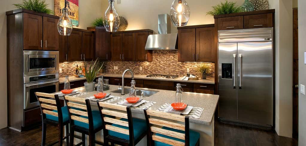 The kitchen's island allows for informal dining and is a great spot for guests to munch on appetizers and socialize during a party.<br /> <br /> The kitchen's backsplash utilizes neutral tones that complement the home's natural surroundings.<br /> <br /> PHOTO COURTESY OF<br /> Dorn Homes<br />