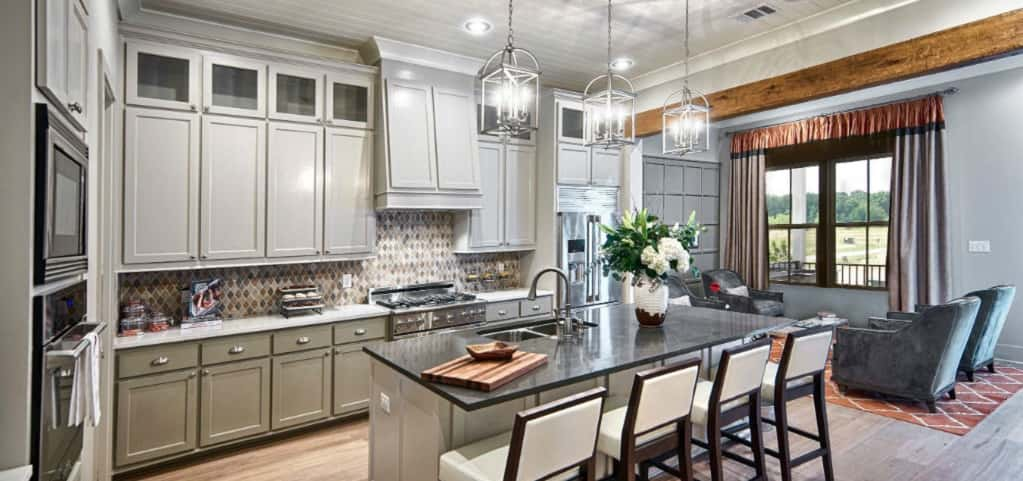 "The home's neutral gray palette is carried over into the spacious kitchen, making it airy and appealing. Three small glass chandeliers adorn the ceiling over the home's spacious and functional granite island.<br /> <br /> White battan board ceilings give the home just a hint of coastal charm. ""The home has a coastal Carolina theme and carries on the craftsman style found in many Carolina homes,"" Rojas says.<br /> <br /> PHOTO COURTESY OF<br /> Level Homes"