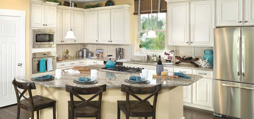 A designer kitchen features granite countertops, a central island and a double sink, all features named by the National Association of Home Builders as the most desirable for 2014. But it's the window at the kitchen sink that earns the most praise from prospective buyers, says Barrett. <br /> <br /> Sleek white cabinets and stainless steel appliances finish off the look while dark hardwood floors help the room pop. X-Back chairs make the perfect companion to the blue and white breakfast spread.<br /> <br /> PHOTO COURTESY OF<br /> David Weekley Homes