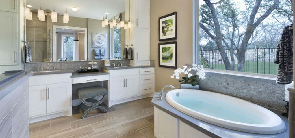 "The master bath is reminiscent of an upscale resort, says Harris. <br /> <br /> ""We've incorporated an oversized shower with a rain showerhead, a luxurious soaking rub and double sinks.""<br /> <br /> An oversized mirror and vanity stool make this room especially conducive to pampering, while a sizeable window makes for a natural spa-like experience.<br /> <br /> PHOTO COURTESY OF<br /> Standard Pacific Homes"