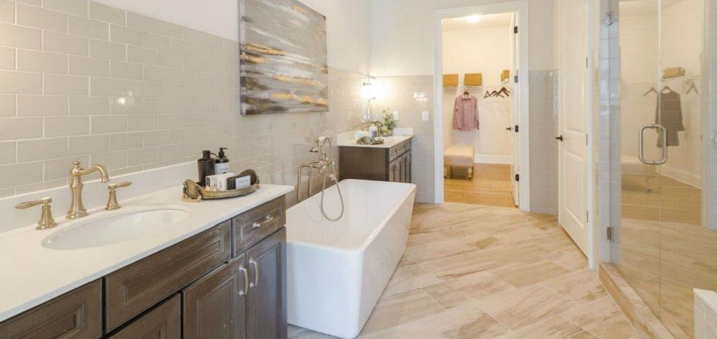 A frameless shower enclosure, quartz countertops and herringbone pattern tile make for a relaxing getaway in the home's master bathroom. The shower is oversized and includes a curbless entry. While the showers are standard, tubs are optional.<br /> <br /> Wiggins says the master bathroom provides access to the laundry room, making it easy to deposit clothes that need cleaning.<br /> <br /> PHOTO COURTESY OF<br /> Edward Andrews Homes