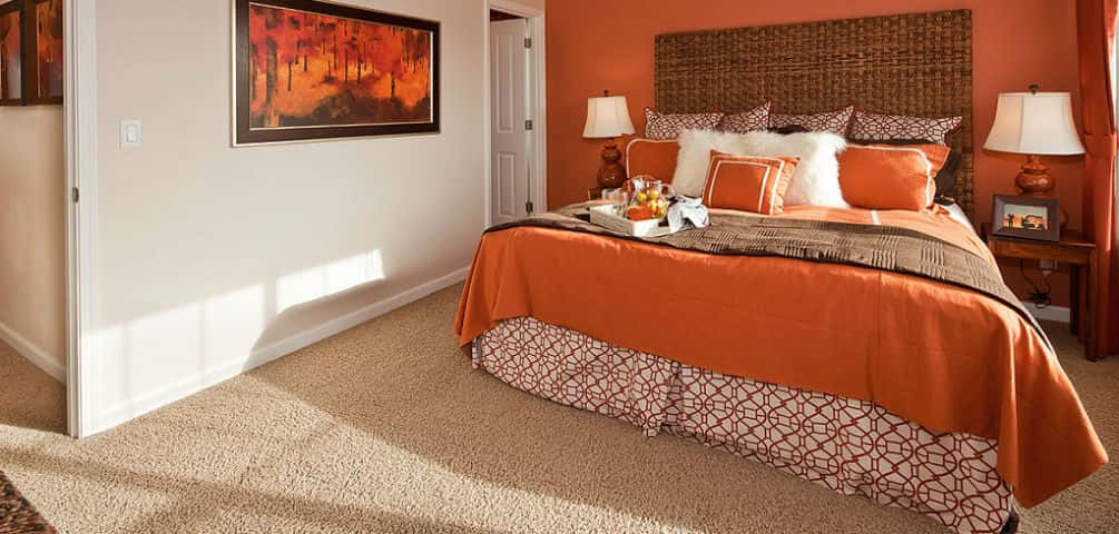 "A basketweave headboard and a combination of orange and white walls brighten up the Residence Two's carpeted owner's suite, located on the third level of the townhome. A laundry closet is conveniently located right outside the bedroom.<br /> <br /> Murphy says the bedroom accommodates a king-sized bed and includes an attached walk-in closet with a window. ""The attached vinyl floored on-suite bath has a ceramic tile surround on the one sink vanity and a double walk-in shower with sliding doors,"" she says.<br /> <br /> PHOTOS COURTESY OF<br /> Centex Homes"