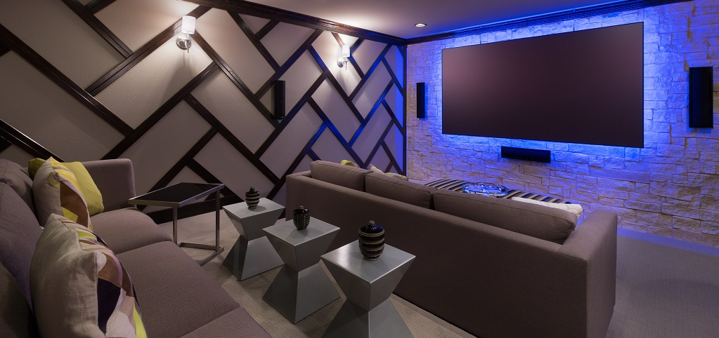 An upstairs media room is an optional feature in the Pinehurst plan. A herringbone-styled wall meets rough white stone to form this sleek cinematic experience. <br /> <br /> A massive flat screen TV and staggered seating with stylish side tables help pull the look together. Sleek sconce lighting and a blue back-lit screen contribute to the modern feel of this room. <br /> <br /> Other optional features in the Pinehurst plan include a downstairs hobby room.<br /> <br /> PHOTO COURTESY OF<br /> Standard Pacific Homes