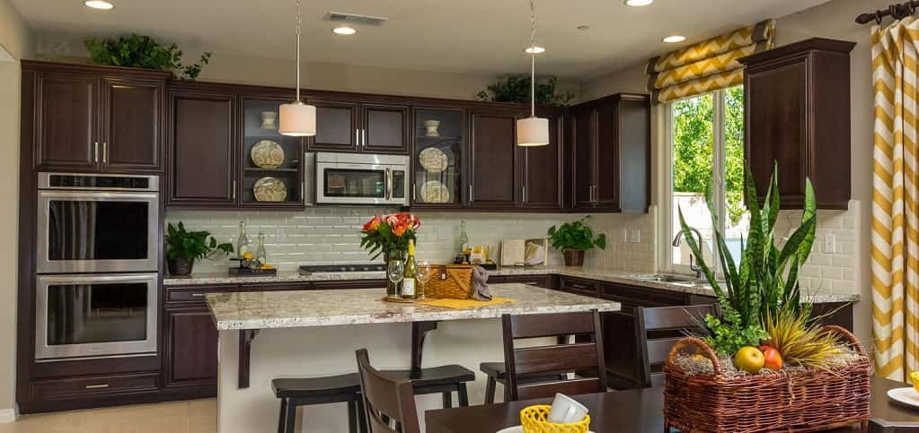 A white subway tile backsplash and contrasting dark brown cabinets give the kitchen a stylish, open feel, while stainless steel appliances and white marble countertops add a modern touch. Glass doors on two of the cabinets allow buyers to showcase special pieces.<br /> <br /> The large kitchen island provides space for cooking and baking or for a quick bite to eat, while a breakfast nook is the place where families can enjoy meals in a less formal space than the dining room. A hidden pantry adds valuable storage space to the area.<br /> <br /> PHOTO COURTESY OF<br /> Michael Gregory Builders