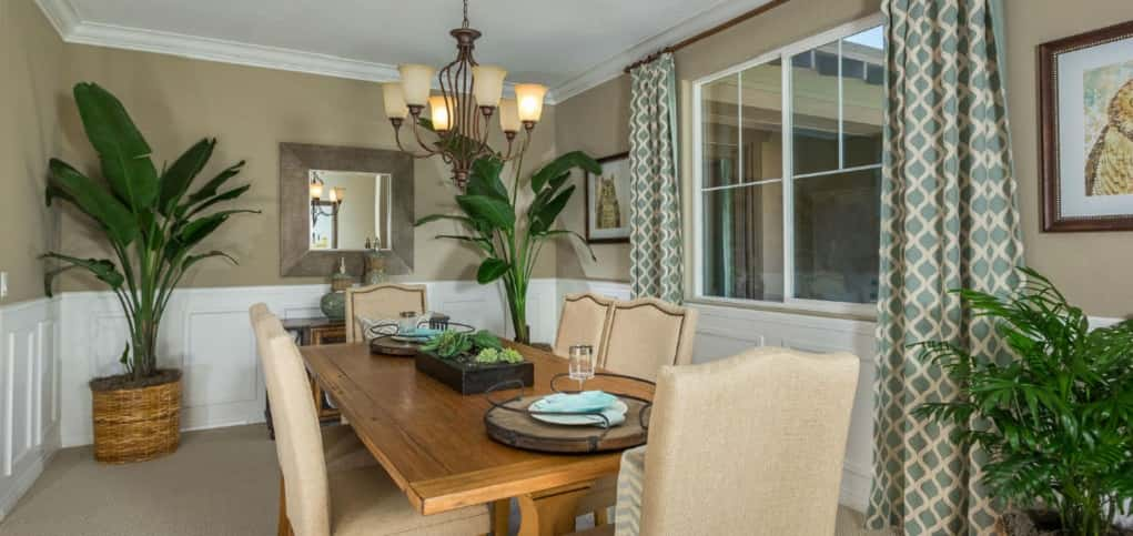 Two large windows provide natural light to the Plan 1's spacious, yet intimate dining room. White crown molding and wainscoting coupled with a neutral tan color on the walls is neither overpowering nor understated.<br /> <br /> Opening to the home's foyer, the space is away from the kitchen and great room, but spacious enough for hosting large groups of guests and intimate enough for smaller dinner parties.<br /> <br /> PHOTO COURTESY OF<br /> Michael Gregory Builders