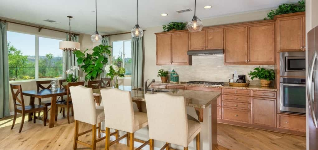 With a large island in the center of the kitchen, the kitchen is functional and artfully designed. A tan glass tile backsplash keeps the space light and airy, while stainless steel appliances keep the look fresh.<br /> <br /> Open to the breakfast nook and great room (not shown), the home's kitchen provides a place for cooks, guests and family to congregate during parties or holidays. A hidden pantry helps prevent clutter by providing valuable storage space.<br /> <br /> PHOTO COURTESY OF<br /> Michael Gregory Builders