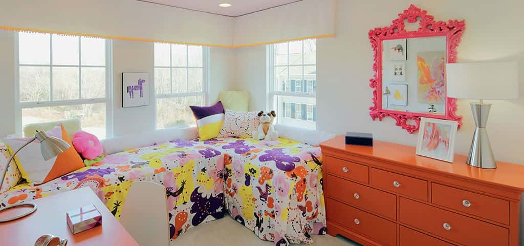 "Found in the Signal Hill Station community by <a href=""https://www.newhomesource.com/builder/miller-and-smith/about/19660"" target=""_blank"" title=""Learn More About Miller and Smith"">Miller & Smith</a>, this young girl's room pops with color. Perfect for any flower fanatic, this space features bright and vibrant hues that will make her feel at home.<br /> <br /> Copy the look in your home by finding the perfect bedspread and pairing it with some unique furniture accents. Bright orange dresser with a matching desk? Totally!<br /> <br /> PHOTO COURTESY OF<br /> Miller and Smith"
