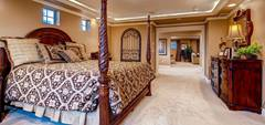 This spectacular bedroom has a king-sized bed lying on a bedframe with tapering twisted wood at the foot edges.