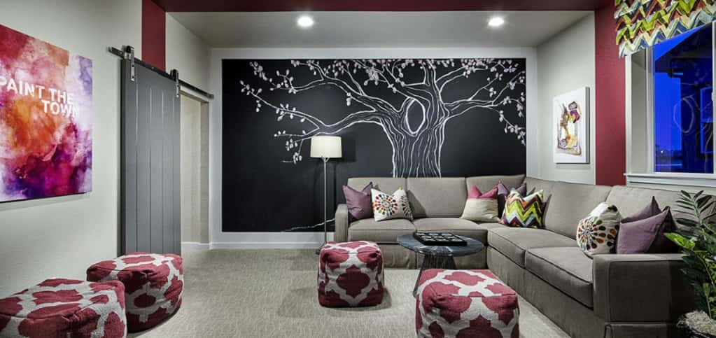 "The home's loft can be used for any purpose, but here the loft is used as a kids' playroom that can double as a homework or hangout area. A large sectional sofa and four ottomans provide plenty of seating in this space, while a large black accent wall includes a chalk-like drawing of a cherry blossom tree.<br /> <br /> A barn door, one of the latest home trends, can easily be closed to prevent noise leakage. ""Most buyers install a barn door, as it creates a separate space for their kids that can be closed off, if necessary,"" Haflich says.<br /> <br /> COURTESY OF<br /> Shea Homes"