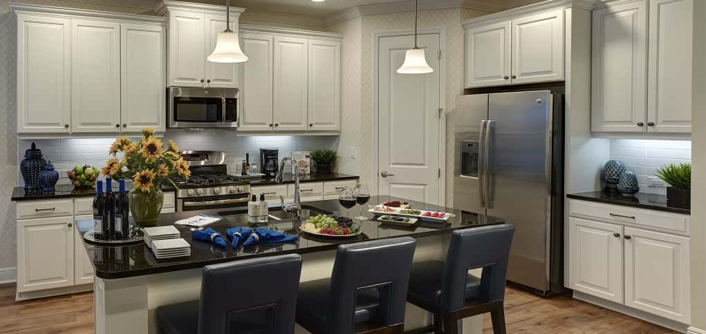 "A large kitchen island is the hub of this spacious kitchen, outfitted with white cabinets and light-colored wood floors. ""The kitchen is designed to be functional as well as beautiful,"" Bowman says. ""This is a real cook's kitchen and it also provides enough space for 'workers' in the kitchen who can help too.""<br /> <br /> A main draw for buyers is the option to open up the kitchen's walk-in pantry to a butler pantry that goes into the laundry room, which provides plenty of space for storage.<br /> <br /> PHOTO COURTESY OF<br /> Neal Communities"